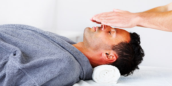 Man receiving Reiki therapy