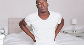 African-American male sitting on edge of bed holding back in pain
