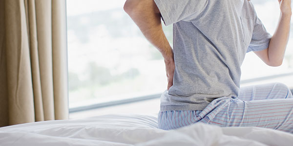 Man on bed with back pain