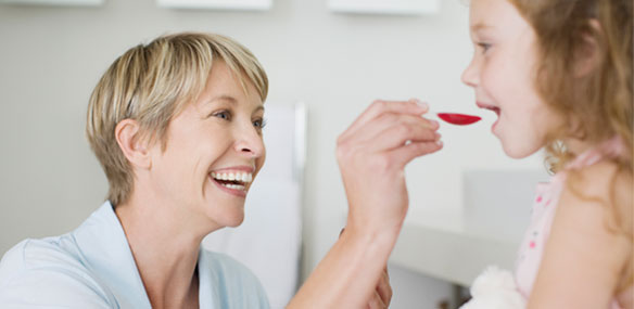 Mother giving daughter spoonful of medicine