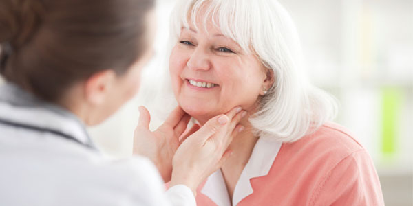 Doctor examining senior woman's neck