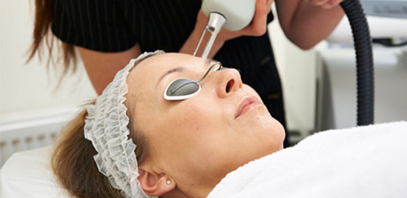 Woman receiving laser light therapy on face