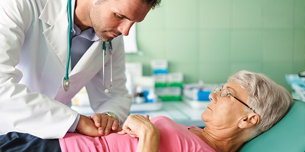 Doctor examining senior woman's stomach