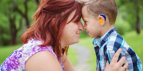 Mother and son wearing a hearing aid in a park