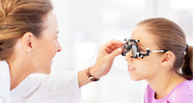 Optician examining girl