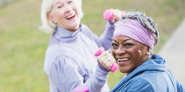 Middle-aged women lifting weights while on walk