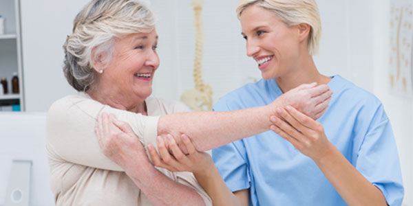 Elderly woman being assisted by nurse with arm stretching exercises