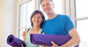 Mature couple holding yoga mats