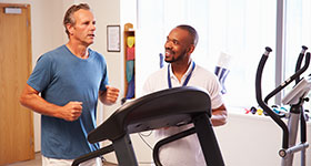 Man exercising on treadmill with physical therapist