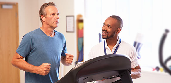 Middle aged man exercising on treadmill with physical therapist
