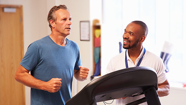 Physical therapist working with patient on treadmill