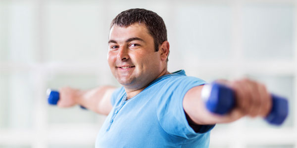 Overweight man using free weights