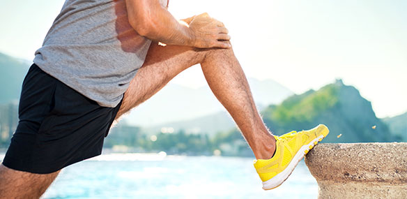 Man stretching leg before run