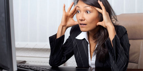 Asian woman stressed looking at office computer