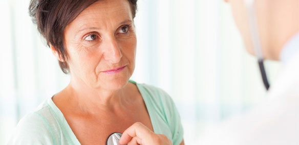 Doctor listening to heart of middle-aged woman