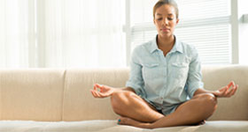 African-American woman meditating on couch at home