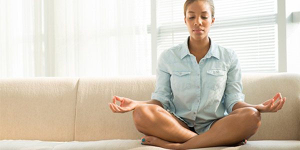 Young woman meditating on couch in home