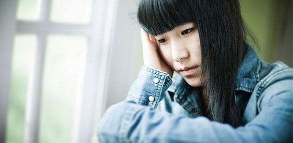 Sad Asian teen female looking out window