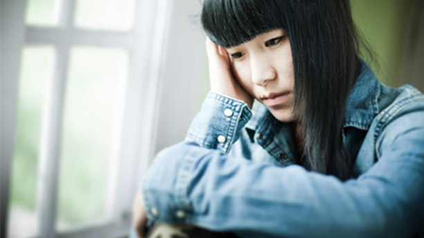 Female Asian teenager with sad expression looking out window