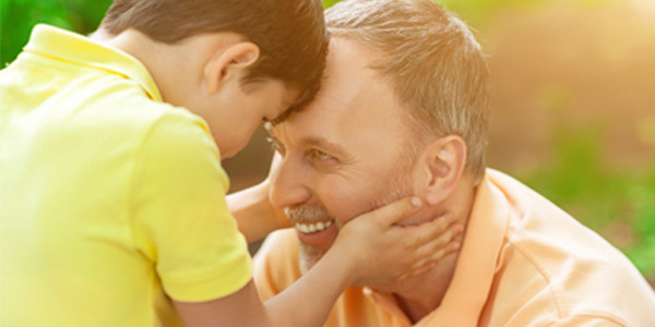 Child holding happy mature man's face