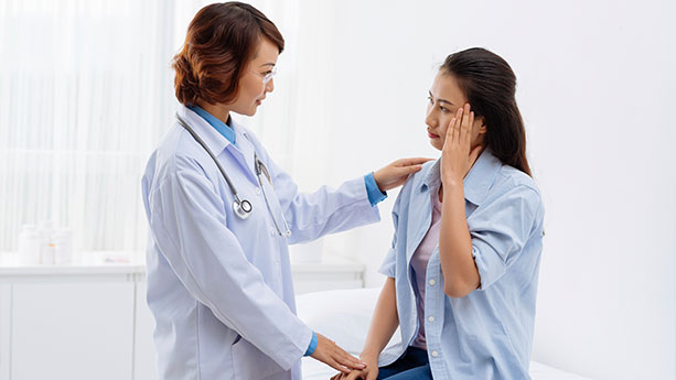 Asian doctor and female patient with headache