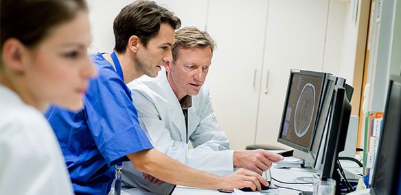Two doctors discussing ct head scan on computer screen