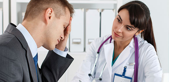 Male patient with headache describing symptoms to female doctor