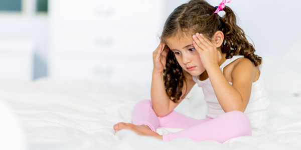Young girl sitting on bed holding head