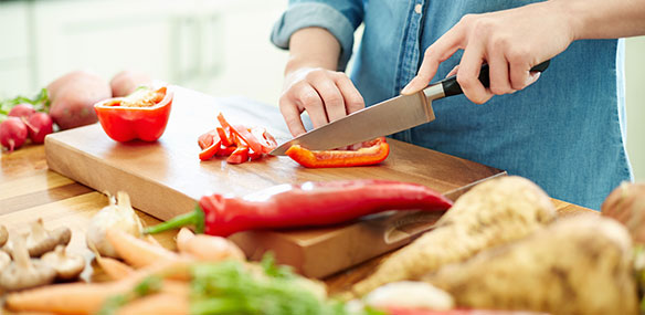 Close up of woman chopping vegetables in kitchen