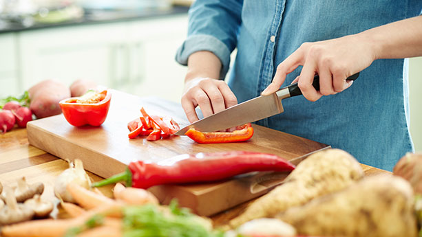 Close up of woman cutting vegetables in kitchen
