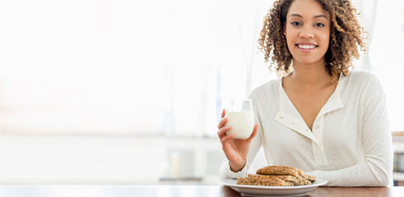 African-American woman sitting at table eating breakfast