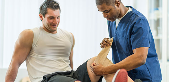 Male patient with doctor having knee wrapped