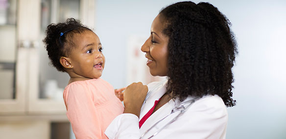African american doctor holding African american baby girl