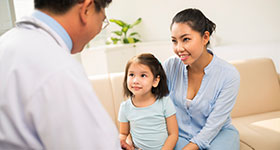 Asian male doctor consulting with mother and daughter