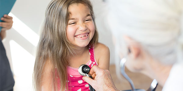 Doctor listening to hispanic girl's heart