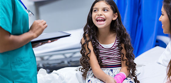 Little girl laughing in hospital with arm cast