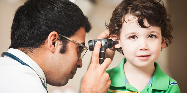 Male doctor examining little boy's ear