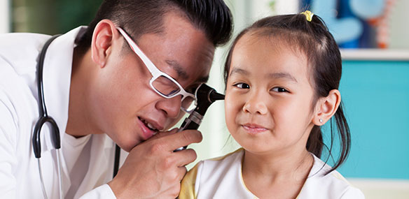 Pediatrician examining girl's ear