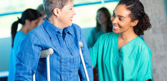 Mature woman on crutches with attendant