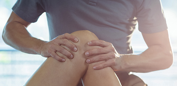 Physical therapist examining knee