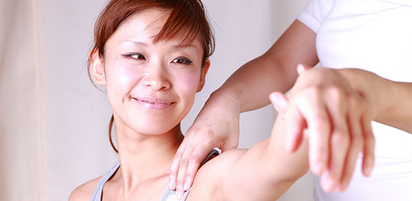 Asian woman getting shoulder massaged