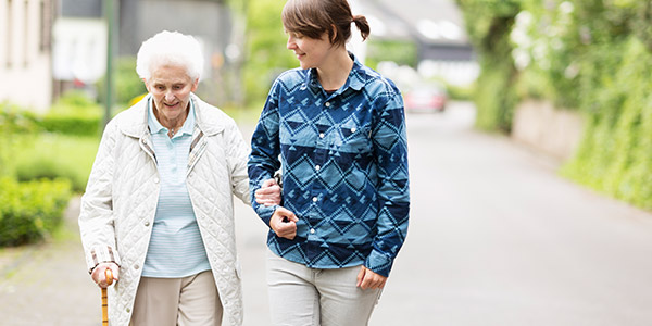 Elderly woman and caregiver walking