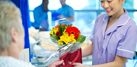 volunteer delivering flowers to elderly patient