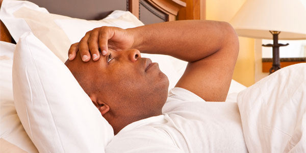 African American man sleepless in bed