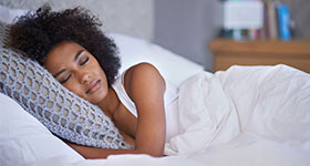 Black woman peacefully asleep in bed