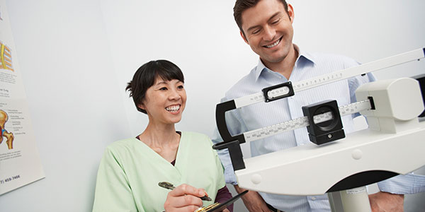 Nurse checking male patient's weight on scale