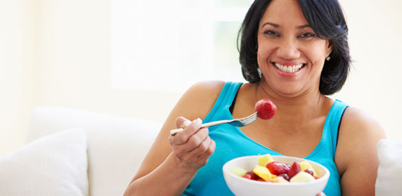 Overweight African-American woman eating bowl of fruit