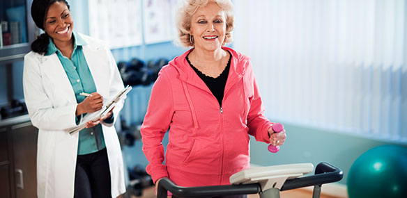 Overweight senior woman exercising on treadmill with doctor supervision