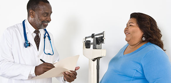 African-American doctor weighing overweight woman