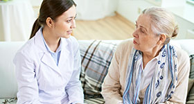 Female doctor and older patient having serious conversation